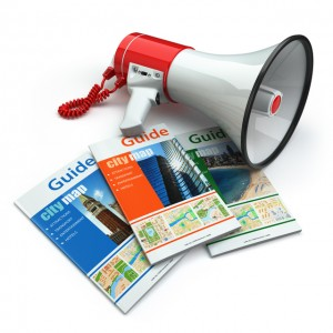 Travel guide books and megaphone on white isolated background.
