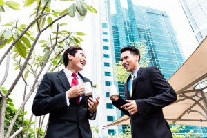 Asian businesspeople drinking coffee outside